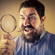 Man looking through a  magnifying glass - PhotoDune Item for Sale