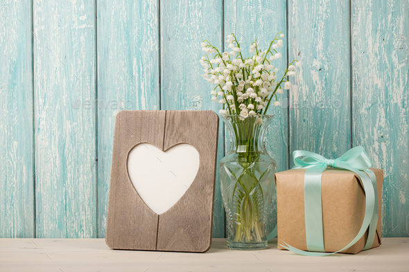 Fresh lilies of the valley, heart shaped frame and gift box - Stock Photo - Images
