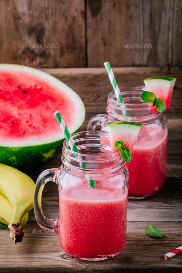 Watermelon and banana  smoothie in mason jars with mint on wooden background - Stock Photo - Images