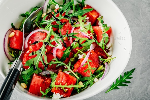 Watermelon with feta, arugula, onion, pine nuts and balsamic sauce. - Stock Photo - Images