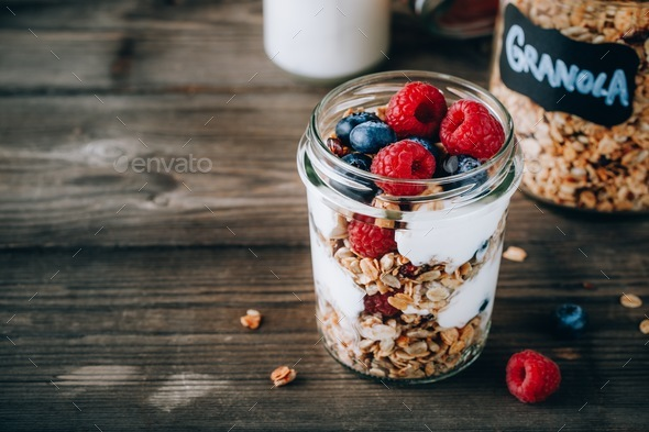 Healthy blueberry and raspberry parfait with greek yogurt in glass mason jar on wood background - Stock Photo - Images