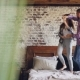Happy Young Lovers Dancing on Double Bed Having Fun in Bedroom and Laughing Carelessly - VideoHive Item for Sale