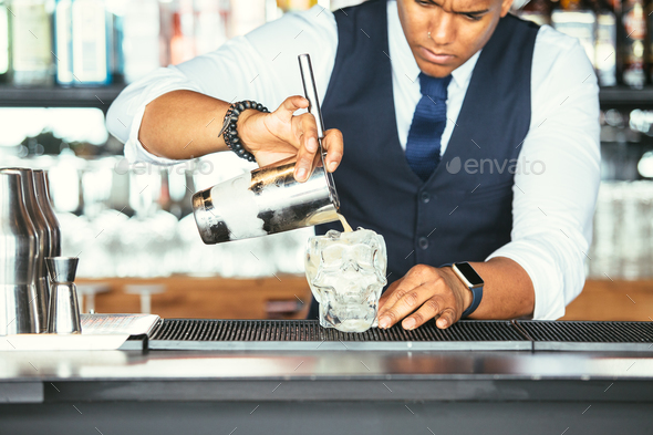 Cropped view of a bartender adds cocktail to a glass - Stock Photo - Images