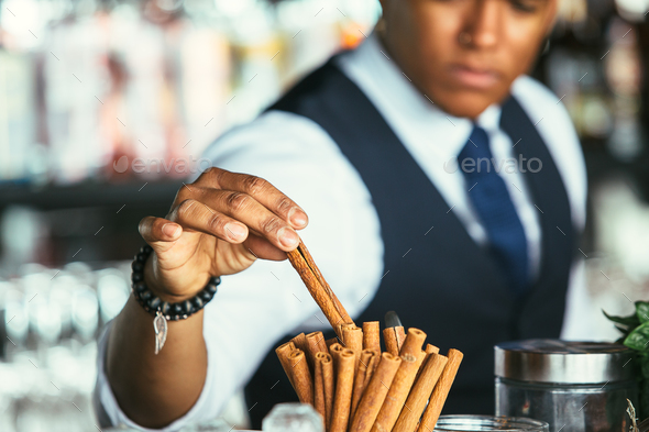 Detail of the hand of a bartender takes cinnamon stick - Stock Photo - Images
