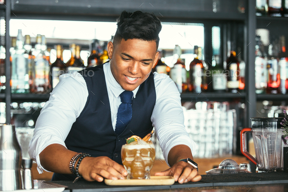 Smiling bartender presenting a cocktail - Stock Photo - Images