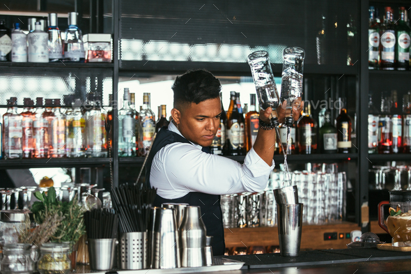 Expert barman adding alcohol to a shaker - Stock Photo - Images