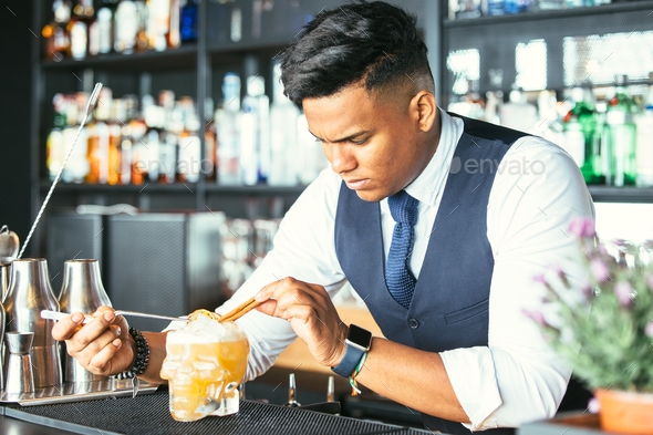 Expert barman decorating a cocktail - Stock Photo - Images
