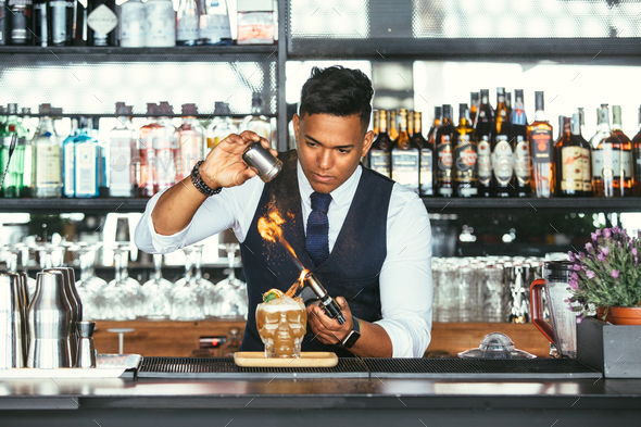 Concentrated expert bartender uses a blowtorch for a cocktail - Stock Photo - Images