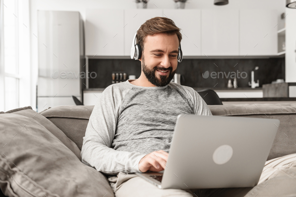 Portrait of a smiling young man in headphones - Stock Photo - Images