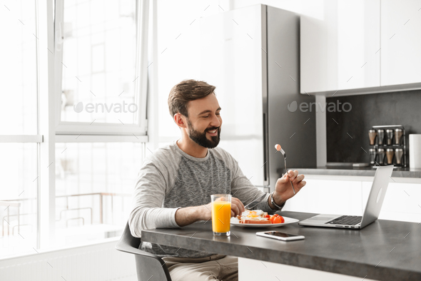 Portrait of a smiling young man having breakfast - Stock Photo - Images