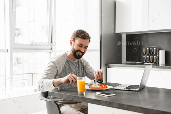 Portrait of a cheerful young man having breakfast - Stock Photo - Images