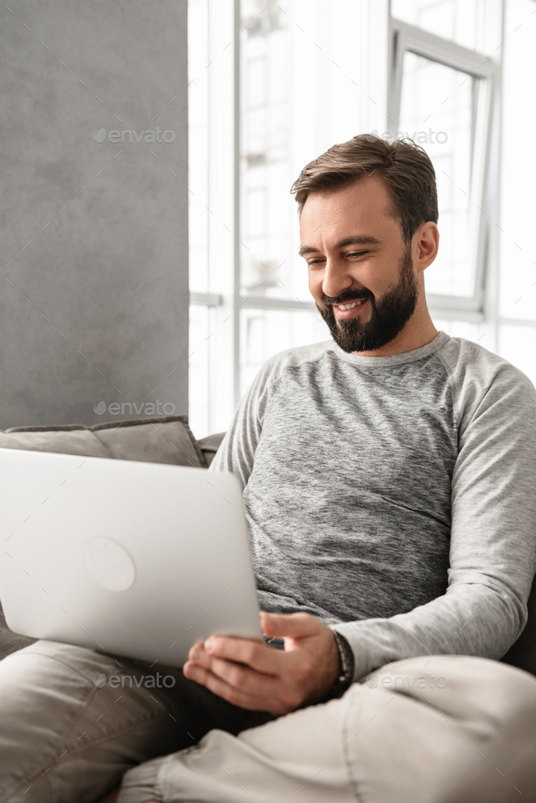 Portrait of a smiling young man working on laptop - Stock Photo - Images