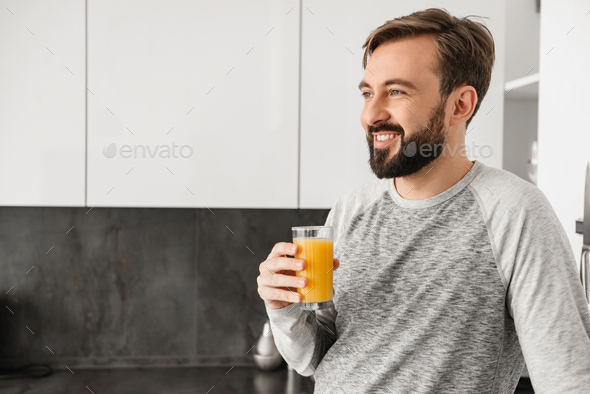 Portrait of a happy young man holding glass - Stock Photo - Images