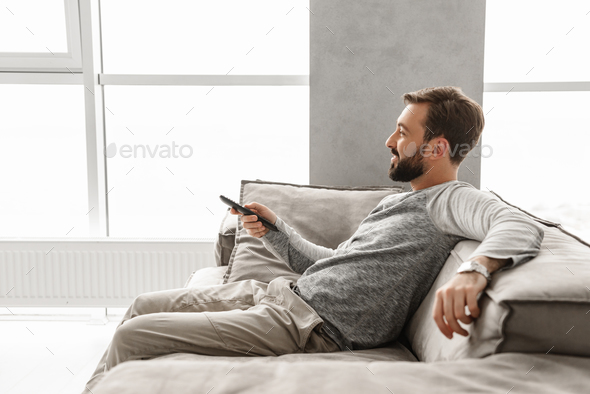 Portrait of a cheerful young man holding TV remote control - Stock Photo - Images