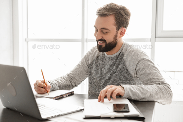 Portrait of a smiling young man working - Stock Photo - Images