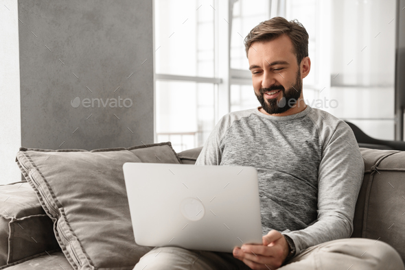 Portrait of a happy young man working on laptop computer - Stock Photo - Images