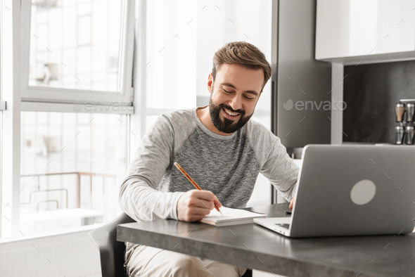 Portrait of a smiling young man working on laptop computer - Stock Photo - Images