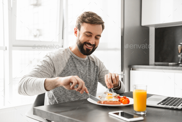 Portrait of a handsome young man having breakfast - Stock Photo - Images
