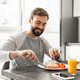 Portrait of a handsome young man having breakfast - PhotoDune Item for Sale