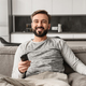 Portrait of a smiling young man holding TV remote control - PhotoDune Item for Sale