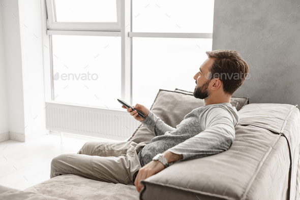 Portrait of a smiling young man holding TV remote control - Stock Photo - Images