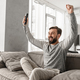 Portrait of an excited young man holding TV remote control - PhotoDune Item for Sale