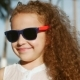 Portrait of a Happy Cute Little Girl Child with Curly Hair and Red Sunglasses Looking - VideoHive Item for Sale