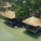 Summer Houses with Thatched Roof on Shore in Mountain Lake with Green Water Among Tropical Nature