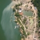 Drone View Boat Pier and Bungalow for Rest on Lake Among Tropical Nature in Mountains. Green Water