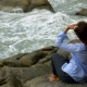 Beautiful Girl in Sunglasses Is Sitting on a Stone Looking in the Water - VideoHive Item for Sale
