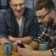 Two Guys Using Entertainment App and Laugh. Happy Young Caucasian Friends Use Smartphone, Have - VideoHive Item for Sale