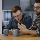 Two European Guys Talk Using Smartphone Together. Business Startup Partners Discuss New Ideas