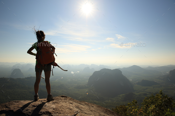 Successful hiker enjoy the beautiful sunrise view on mountain top - Stock Photo - Images