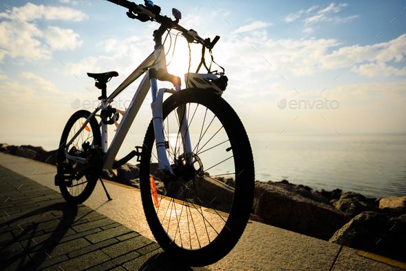 Mountain bike with helmet on sunrise seaside - Stock Photo - Images