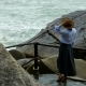 A Girl in a Brown Hat Is Standing on a Stony Bank Looking at the Waves - VideoHive Item for Sale