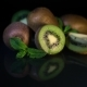 Fruits of Juicy Kiwi Rotate on a Table on a Black Background. - VideoHive Item for Sale