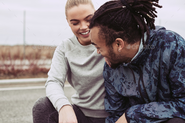 Smiling young couple catching their breath while out jogging together - Stock Photo - Images
