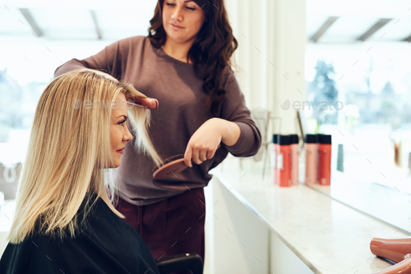 Smiling young woman having her hair straightened in a salon - Stock Photo - Images