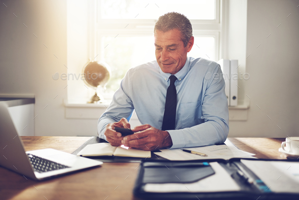 Smiling mature businessman using a cellphone at an office desk - Stock Photo - Images