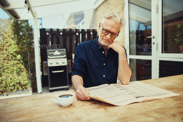 Senior man enjoying a coffee and reading the newspaper outside - Stock Photo - Images