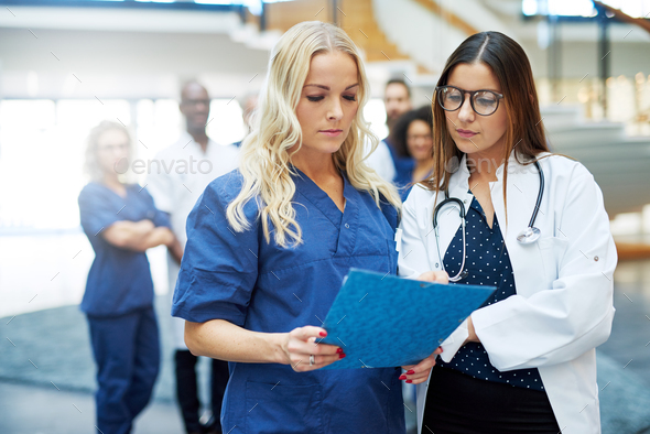 Women in hospital standing and browsing papers - Stock Photo - Images