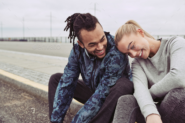 Smiling young couple taking a break from an outdoor run - Stock Photo - Images