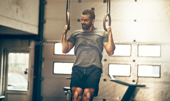 Muscular young man working out on rings at the gym - Stock Photo - Images