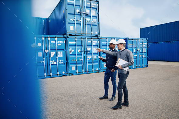 Two engineers tracking shipping inventory in a freight container yard - Stock Photo - Images