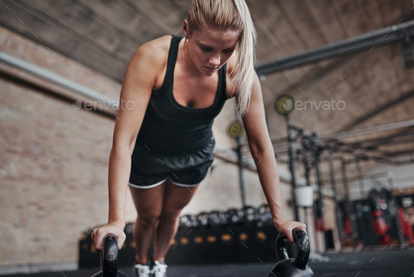 Fit young woman weight training on a gym floor - Stock Photo - Images