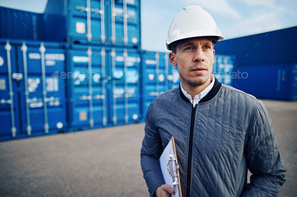 Dock manager standing alone in a commercial shipping yard - Stock Photo - Images