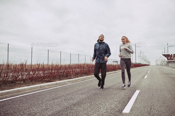 Diverse young couple in sportswear jogging on a country road - Stock Photo - Images