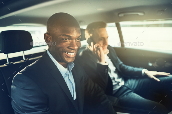 Smiling African businessman driving with a colleague to work - Stock Photo - Images