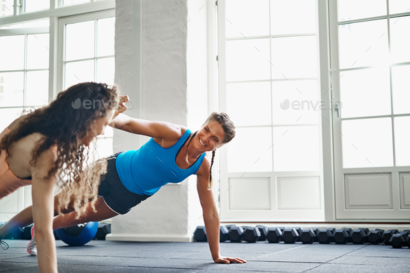 Smiling friends high fiving while doing pushups in a gym - Stock Photo - Images