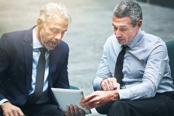 Mature business colleagues talking together and using a digital tablet - Stock Photo - Images